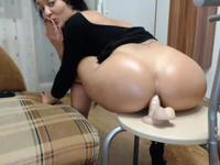 Raven haired beauty sits on a dildo