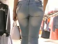 Two girls in the tight blue jeans are strolling over the shops followed by camera man