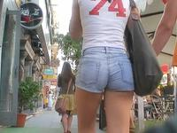 The cameraman was strolling around the city recording amateurs in the hot jeans shorts