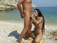 Brunette milf sucks a dick on a beach